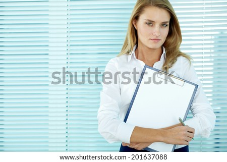 Portrait of young businesswoman with clipboard looking at camera  - stock photo