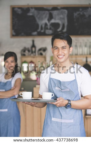 portrait of young cafe staff at work standing and holding a tray with two cup of coffee