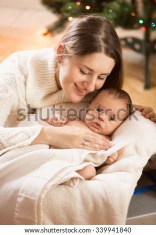Portrait of young caring mother with newborn baby lying in basket - stock photo