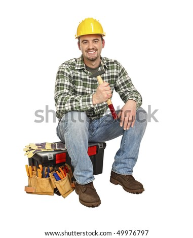 portrait of young  carpenter sit on his toolbox - stock photo