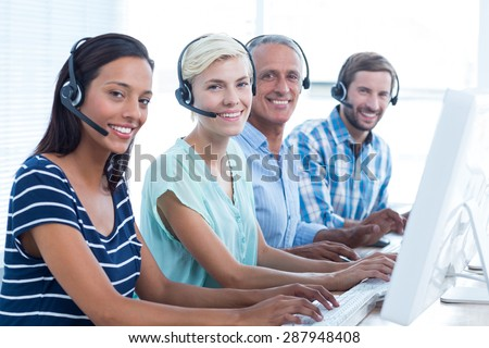 Portrait of young casual call centre looking at the camera - stock photo