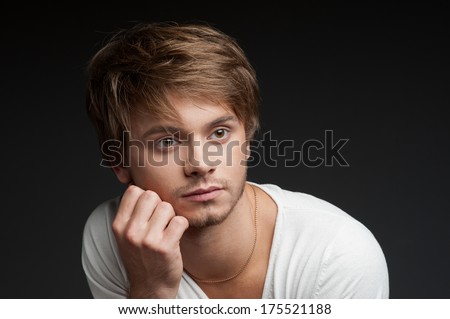 portrait of young casual caucasian man in white t-shirt over gray background - stock photo