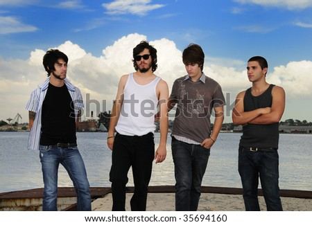 Portrait of young casual group of friends posing outdoors - stock photo