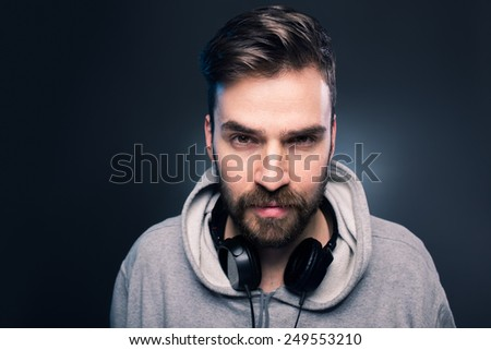 Portrait of young casual man with headphones around the neck. Studio shot on gray background. - stock photo