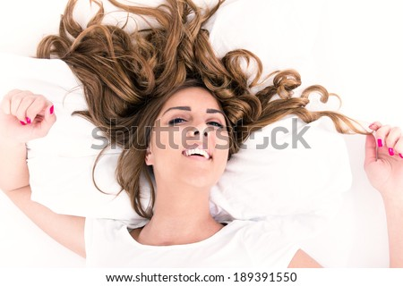 portrait of young casual woman lying in bed with hair spread around, domestic atmosphere - stock photo
