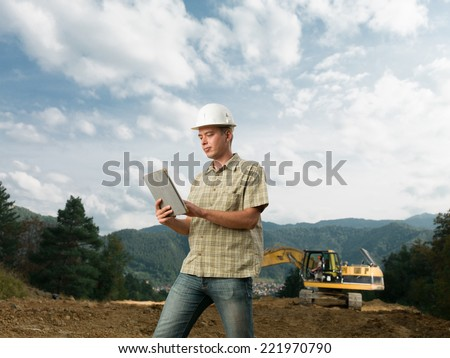 portrait of young caucasian architect standing on construction site holding digital tablet - stock photo