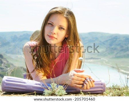 Portrait of young caucasian beautiful sport women lying on travel mat  in summer nature on the background of river