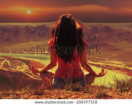 Portrait of young caucasian beautiful sport  women sitting at lotus pose at sunset background of river in red shirt and blue pants - stock photo