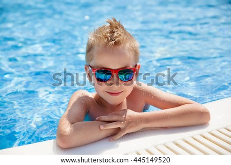 portrait of young caucasian boy in swimming pool - stock photo