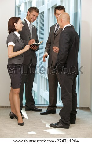 Portrait of young caucasian business people talking in office - stock photo