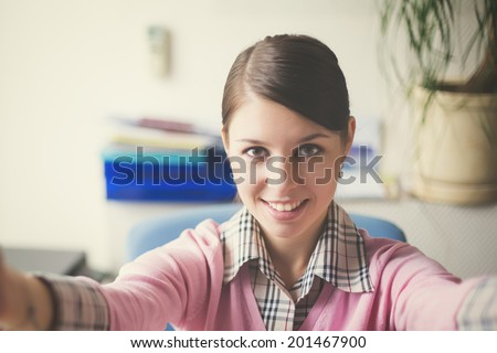 Portrait of young caucasian business woman in pink vest at her office doing selfie - stock photo