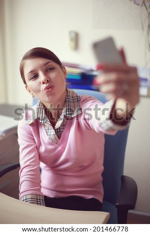 Portrait of young caucasian business woman in pink vest at her office doing selfie on the phone. - stock photo