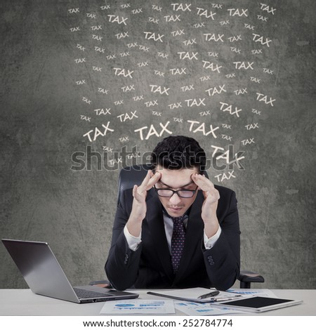 Portrait of young caucasian businessman having headache when counting his tax - stock photo