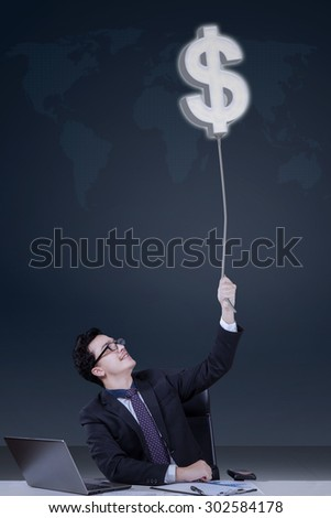Portrait of young caucasian businessperson working with laptop and pulling a dollar symbol - stock photo