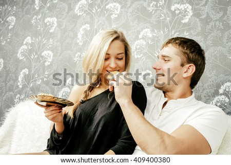 Portrait of young caucasian couple sit on white wool couch together eating cookie Man holding sweet between lips. Woman bite food. Empty texture Copy space for inscription. White and black clothes - stock photo