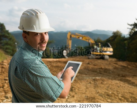 portrait of young caucasian engineer on construction site holding digital tablet - stock photo