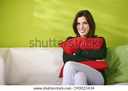 portrait of young caucasian female sitting on white sofa at home and hugging red pillow. Looking at camera and smiling