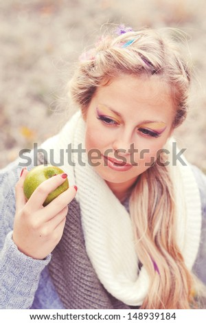 Portrait of young caucasian girl holding green apple outdoors