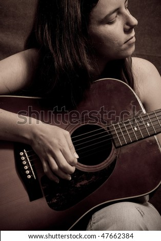 Portrait of Young Caucasian Girl Playing Guitar ( Sepia Toned ) - stock photo