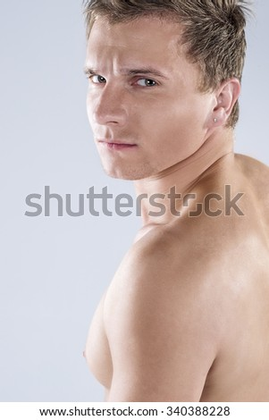 Portrait of Young Caucasian Handsome Man with Naked Torso.Looking Backwards. Against Gray Background. Vertical Image Composition - stock photo