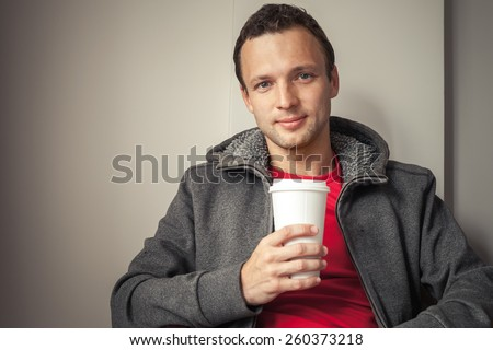 Portrait of young Caucasian man in hoodie sitting in cafe with paper cup of Coffee - stock photo