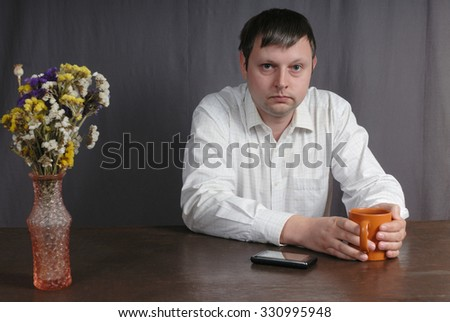 Portrait of young caucasian man in white shirt sitting at the table with the big orange cup of tea and looking directly at You. Man's smart phone and vase with beautiful flowers are on the table too. - stock photo