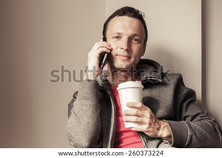 Portrait of young Caucasian man sitting in cafe with paper cup of Coffee. Vintage toned photo, instagram style effect