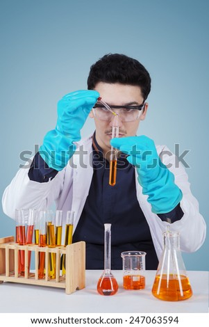 Portrait of young caucasian scientist using glassware and liquid for doing research