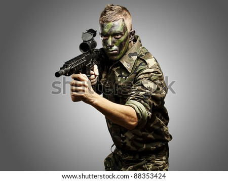portrait of young caucasian soldier with jungle camouflage over grey background - stock photo