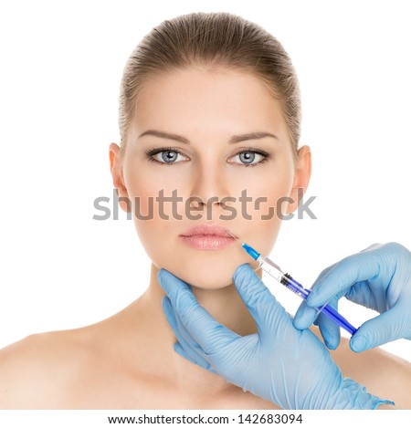 Portrait of young Caucasian woman getting cosmetic injection of botox, isolated over white background. - stock photo