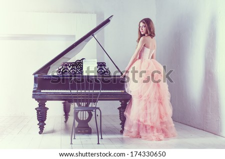 Portrait of young caucasian woman in fluffy dress standing near the grand piano