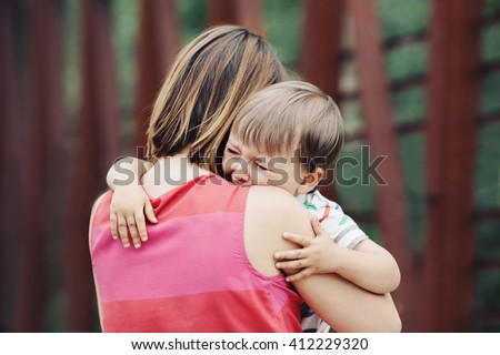 Portrait of  young Caucasian woman mother comforting her crying little toddler boy son outside in park on summer day, parenthood lifestyle concept - stock photo