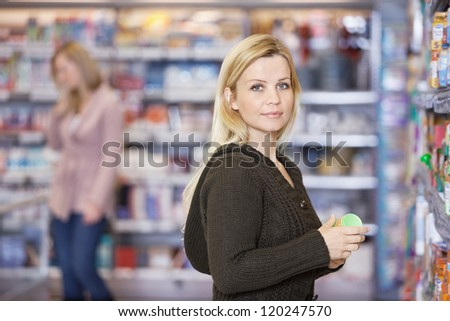 Portrait of young Caucasian woman shopping at supermarket - stock photo