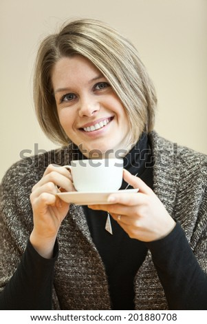 Portrait of young Caucasian woman with coffee cup in hands - stock photo