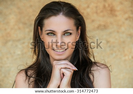 Portrait of young charming cheerful woman propping up her face against beige background.