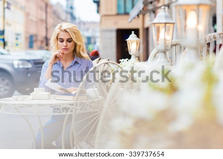 Portrait of young charming elegant lady reading book while sitting in sidewalk cafe during free time, beautiful woman student relaxing in coffee shop in the fresh air after lectures in University - stock photo
