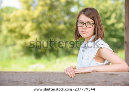 Portrait of young charming sad brunette woman with head laid on her arms at summer green park. - stock photo