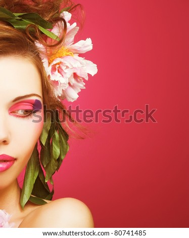 Portrait of young charming woman with  flowers in her hair on the pink background