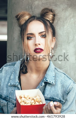 Portrait of young cheeky woman eating popcorn