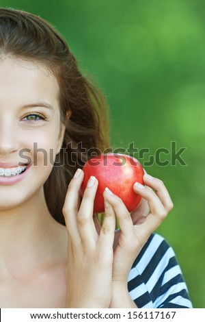 Portrait of young cheerful attractive smiling woman eating red ripe apple at summer green park.