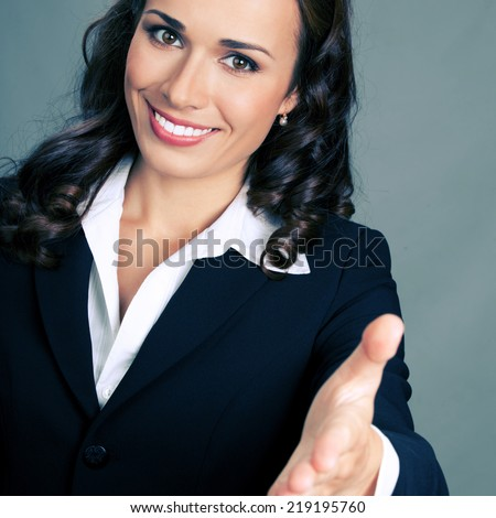 Portrait of young cheerful beautiful business woman giving hand for handshake, over grey background - stock photo