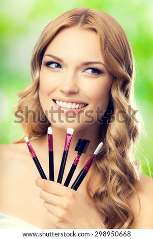 Portrait of young cheerful blond lovely woman with make up tools, outdoors. Beauty, visage and cosmetics concept. - stock photo
