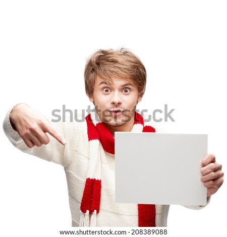 portrait of young cheerful caucasian man which pointing at sign with funny expression - stock photo