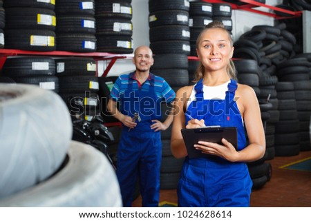 Portrait of young cheerful diligent mechanic girl in coveralls having cardboard with documents in hands at car service