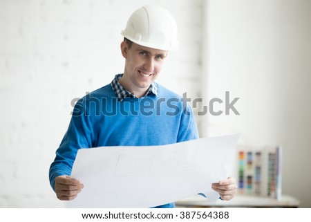 Portrait of young cheerful handsome engineer in white helmet holding blueprint, standing in architectural agency office. Friendly smiling attractive Caucasian model posing with project draft - stock photo
