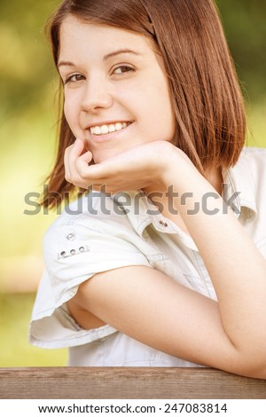 Portrait of young cheerful happy brunette woman wearing white chemise at summer green park. - stock photo