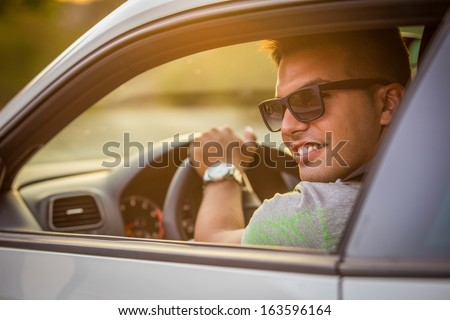 Portrait of young cheerful male in car - stock photo