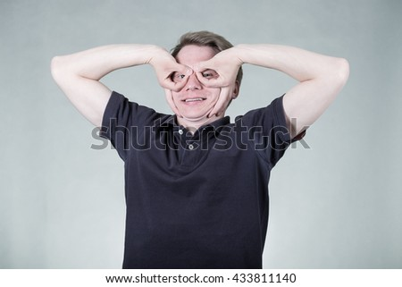 Portrait of young cheerful man with funny gesture on grey background