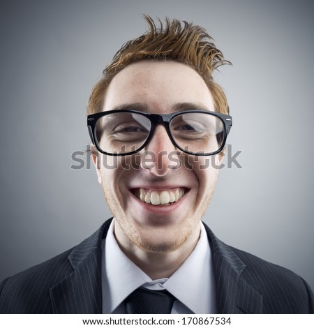 Portrait of young cheerful Nerd businessman smiling