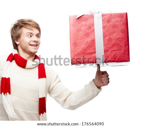 portrait of young cheerful smiling caucasian man which balancing  red christmas gift on thumb with happy smile - stock photo